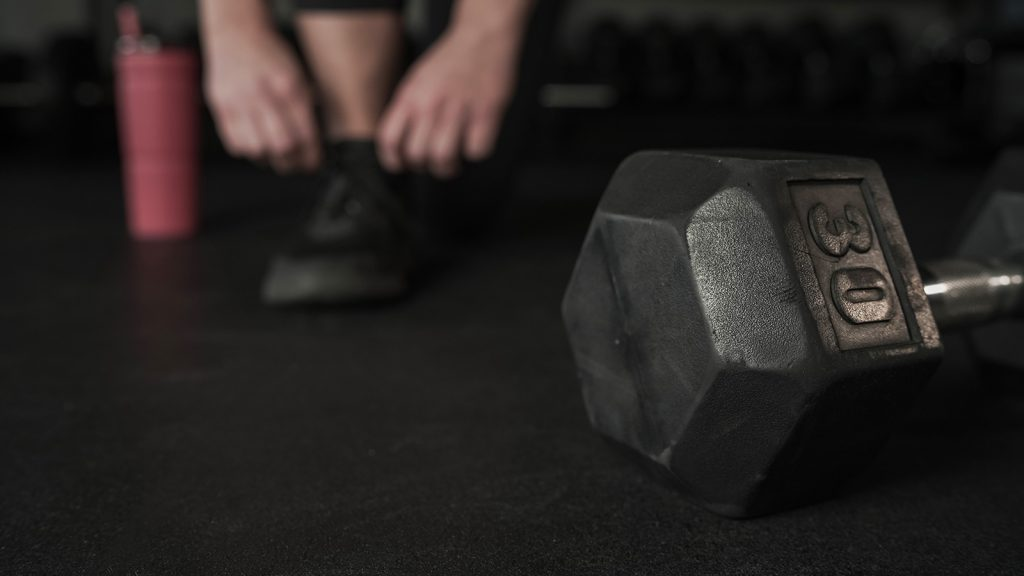 Image of a dumbbell with a person tying their gym shoes in the background.
